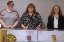 Michelle Legg, Dr. Terri Smith Ruckel, and Jessica Roberts stand behind counter at PRCC