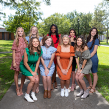 9 girls in dresses standing on sidewalk under trees; PRCC Homecoming Court members for 2021