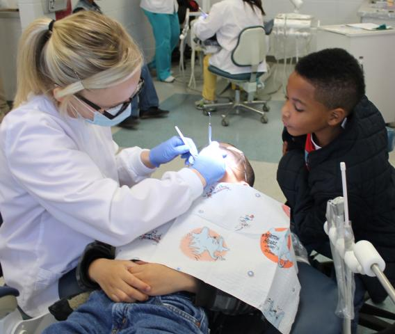 Seven-year-old Nicholas Keys keeps a check on what Pearl River Community College dental hygiene student Chelsea Ford is doing to his friend, Alec McKenzie, during Give Kids A Smile Day at PRCC. The boys attend Grace Christian Elementary School in Hattiesburg.